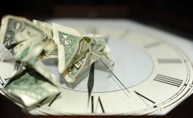 time is money crumpled dollar bills on clock